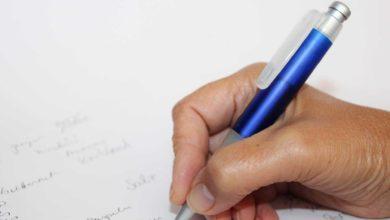 Mavi kalemle beyaz kağıda yazı yazan el