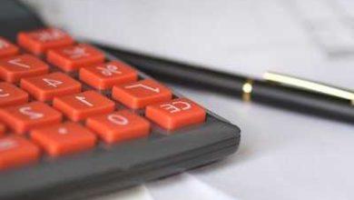 kırmızı tuşlu hesap makinesi ve siyah kalem