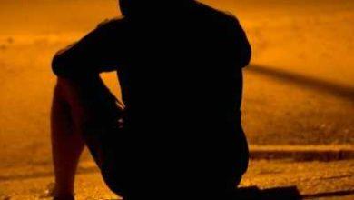 karanlıkta oturan yalnız ve üzgün kişi